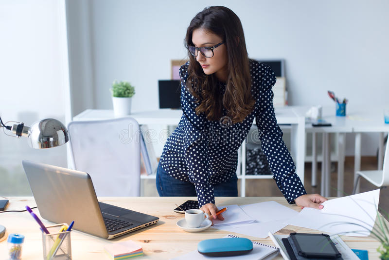 Mooie jonge vrouw die met laptop in haar bureau werken royalty-vrije stock foto