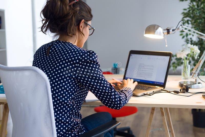 Mooie jonge vrouw die met laptop in haar bureau werken stock fotografie