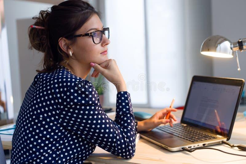 Mooie jonge vrouw die met laptop in haar bureau werken stock afbeeldingen