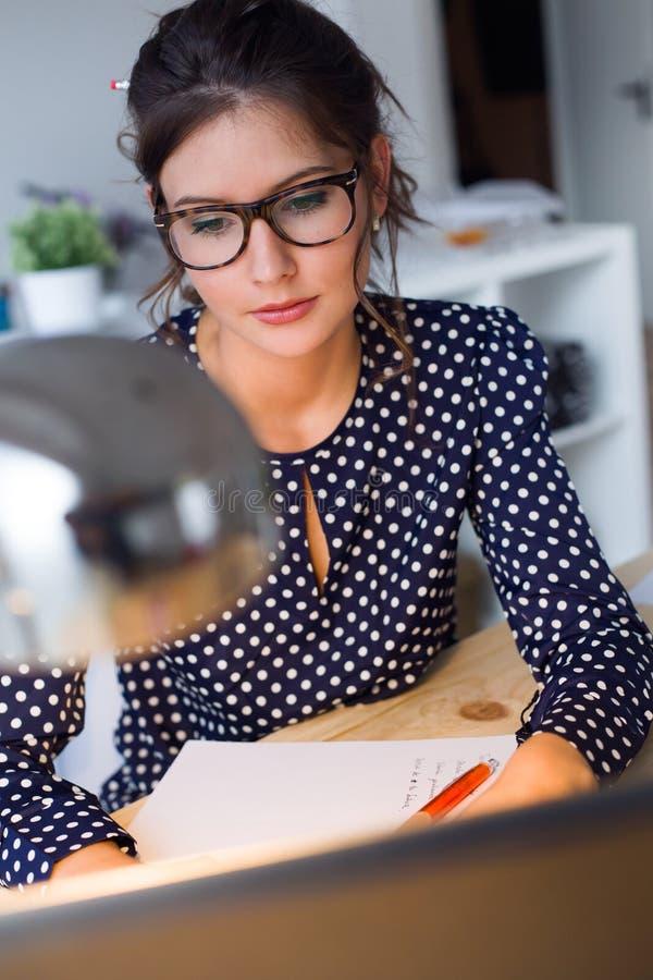 Mooie jonge vrouw die met laptop in haar bureau werken stock afbeelding