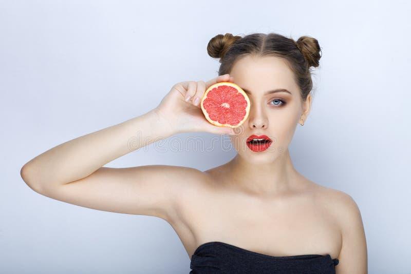 Mooie jonge vrouw die met perfecte gezonde de in make-up naakte schouders van het huid grappige kapsel grapefruit gezonde het ete stock foto's