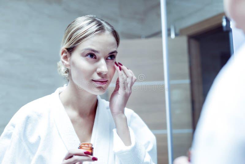 Mooie jonge vrouw die met rode spijkers haar huid op gezicht behandelen stock foto's