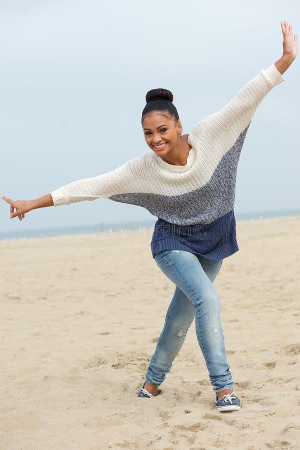 Mooie jonge vrouw die met vrolijke uitdrukking op strand lopen stock afbeeldingen