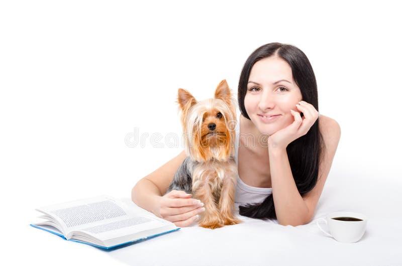 Mooie jonge vrouw die met Yorkshire Terrier ochtendkoffie in bed drinken stock foto's