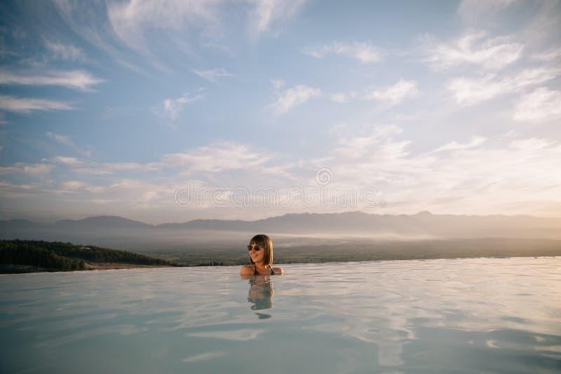mooie jonge vrouw die in natuurlijke pool bij zonsondergang rusten royalty-vrije stock afbeeldingen