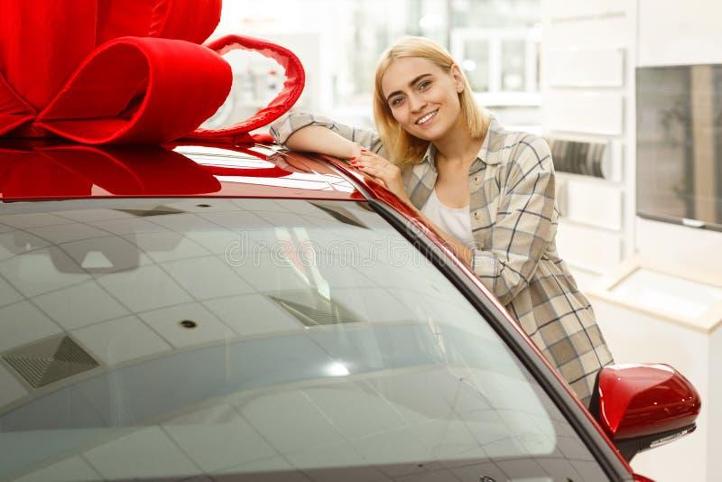Mooie jonge vrouw die nieuwe auto kopen bij het handel drijven stock afbeeldingen