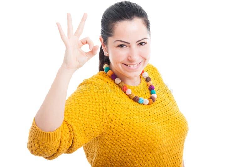 Mooie jonge vrouw die o.k. gebaar tonen stock fotografie
