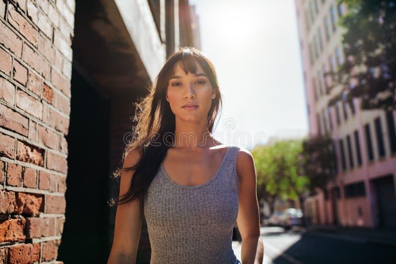 Mooie jonge vrouw die onderaan de stadsstraat lopen royalty-vrije stock foto's
