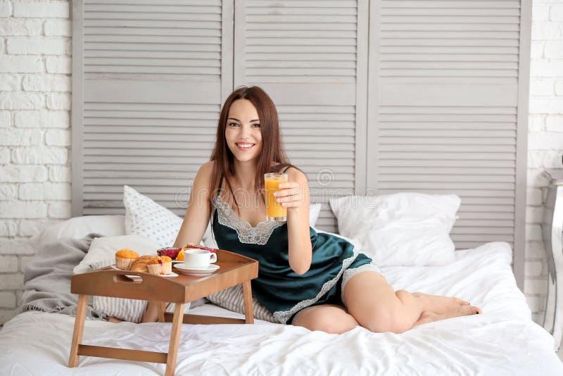 Mooie jonge vrouw die ontbijt op bed hebben thuis stock afbeeldingen