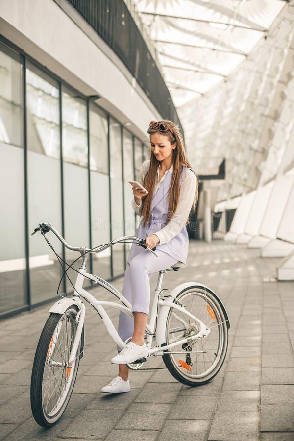 Mooie jonge vrouw die op fiets dichtbij het commerciële centrum situeren stock foto's