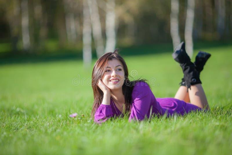 Mooie jonge vrouw die op gras leggen royalty-vrije stock fotografie