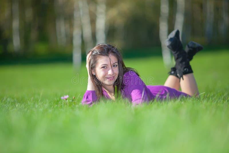 Mooie jonge vrouw die op gras leggen stock afbeeldingen