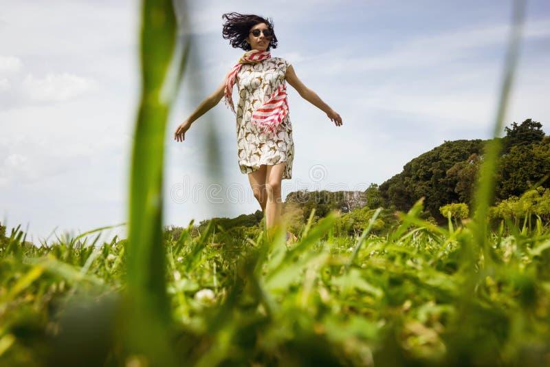 Mooie jonge vrouw die op het groene grasgebied dansen royalty-vrije stock afbeelding