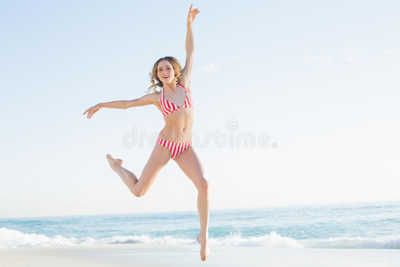 Mooie jonge vrouw die op het strand springen stock foto