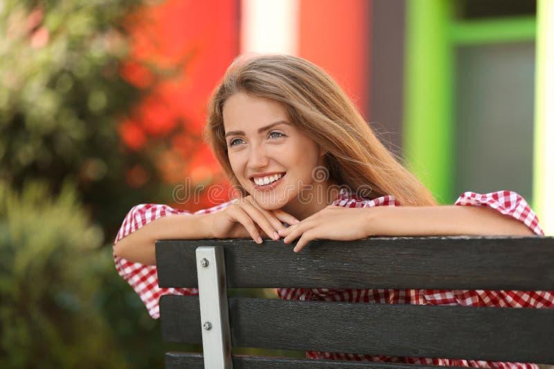 Mooie jonge vrouw die op houten bank in openlucht rust royalty-vrije stock fotografie