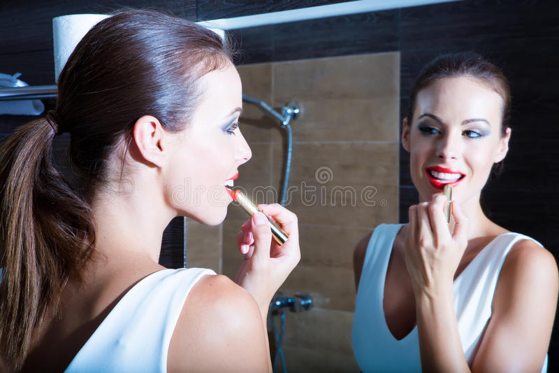 Mooie jonge vrouw die op make-up in de badkamers zetten stock afbeelding