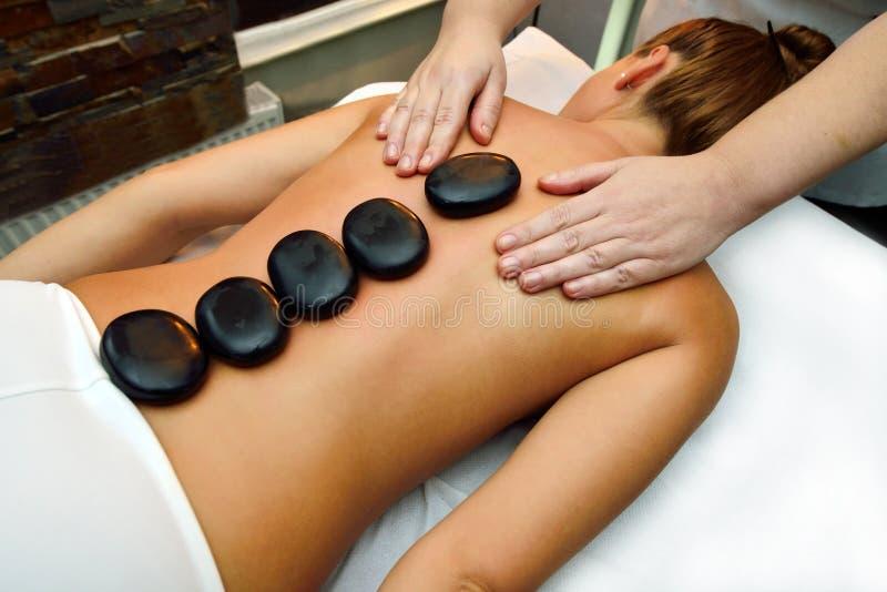 Mooie jonge vrouw die op massagebed liggen stock afbeelding