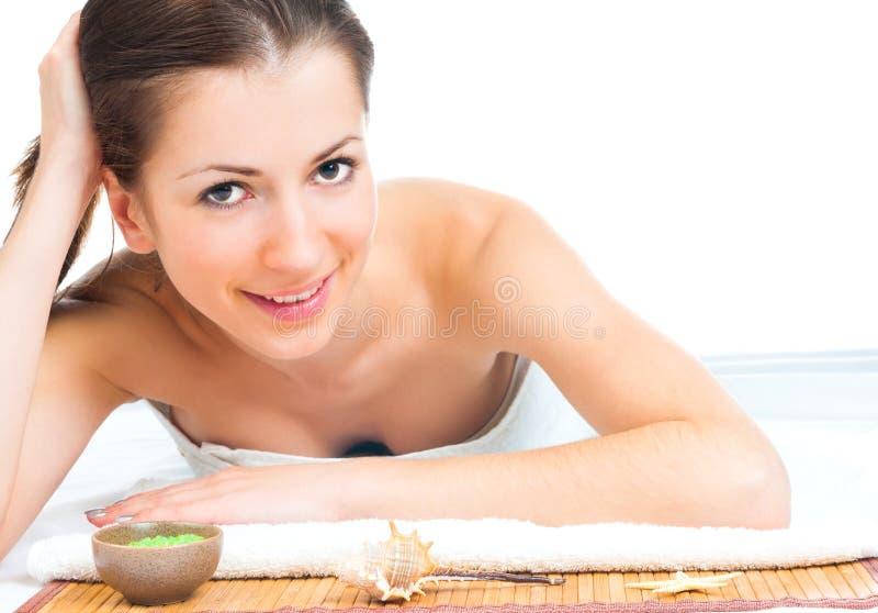 Mooie jonge vrouw die op massagelijst ligt stock afbeeldingen