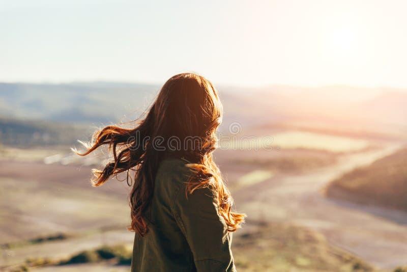 Mooie jonge vrouw die op mooi landschap in zonsondergangtijd glimlachen royalty-vrije stock afbeelding