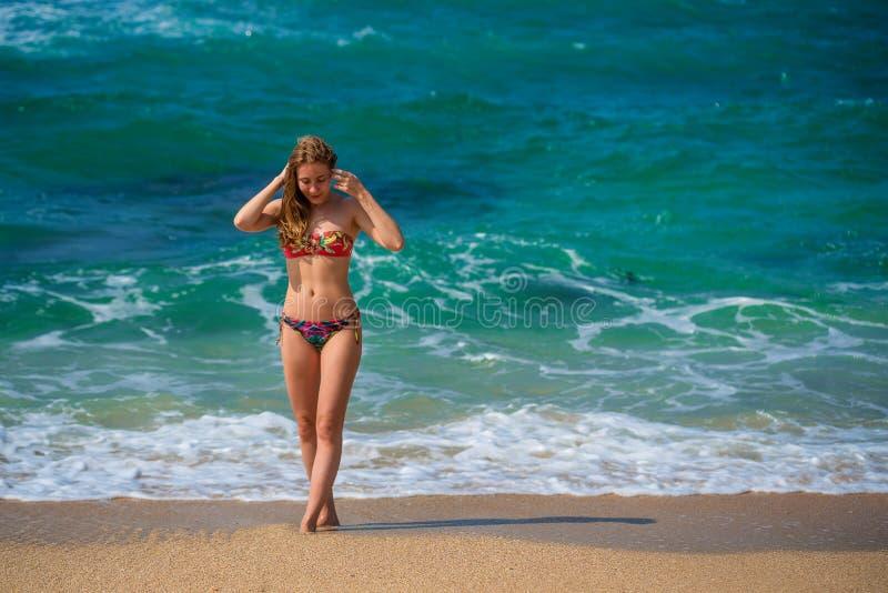 Mooie jonge vrouw die op oceaankust lopen stock afbeeldingen