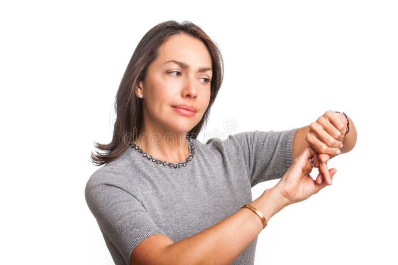 Mooie jonge vrouw die op polshorloge met wijsvinger richten aangezien u recent geïsoleerd gebaar bent stock foto's