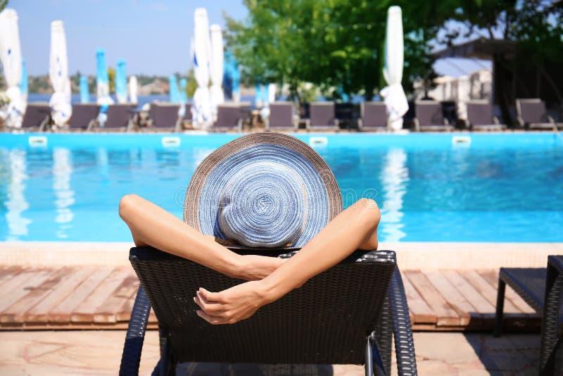 Mooie jonge vrouw die op zonlanterfanter bij toevlucht rusten stock foto