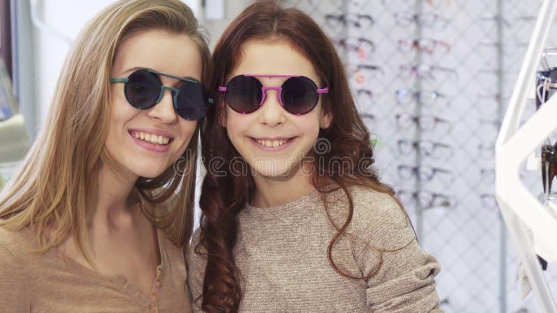 Mooie jonge vrouw die op zonnebril met haar leuke kleine zuster proberen stock afbeeldingen