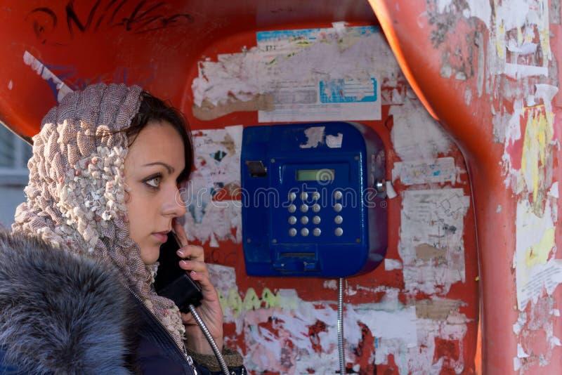 Mooie jonge vrouw die openbare payphone met behulp van royalty-vrije stock afbeelding
