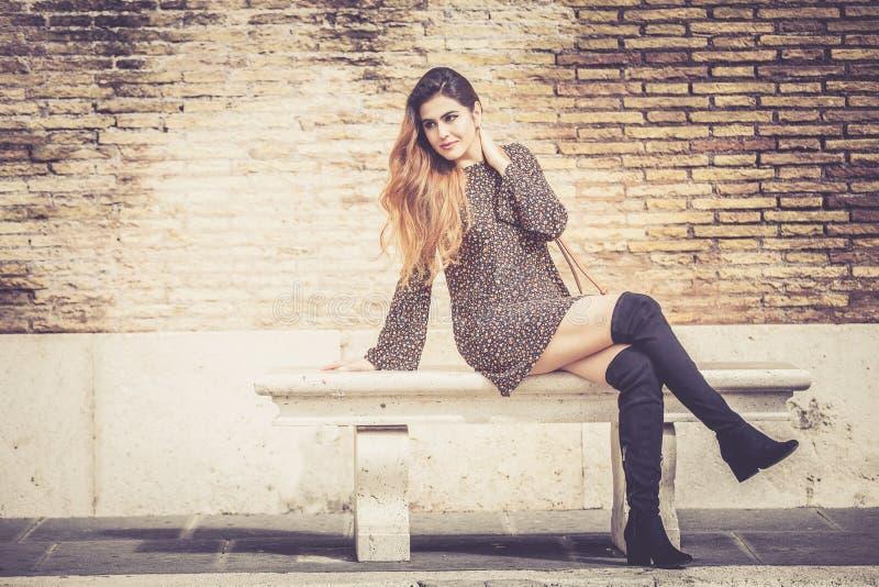 Mooie jonge vrouw die in openlucht op een bank zitten Modieus en sensueel royalty-vrije stock fotografie