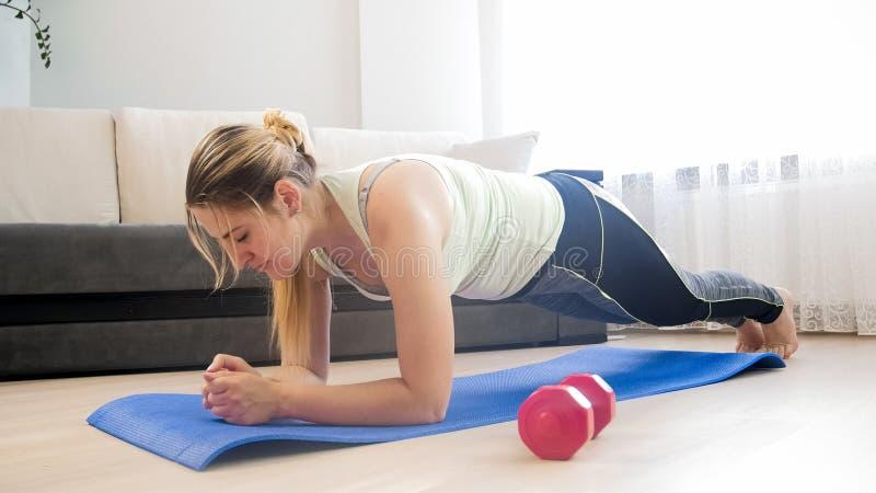 Mooie jonge vrouw die plankoefening op vloer doen bij woonkamer royalty-vrije stock foto