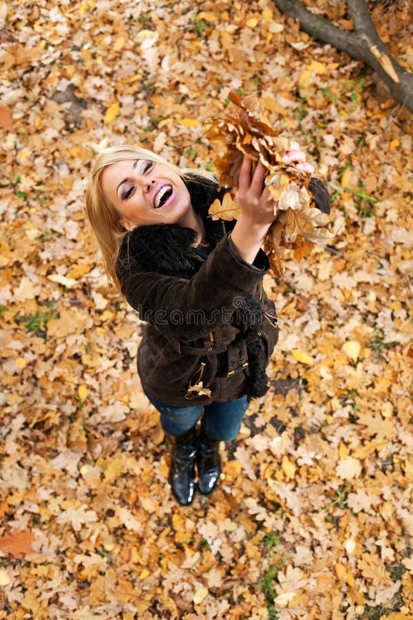 Mooie jonge vrouw die pret in de herfstpark heeft stock afbeelding