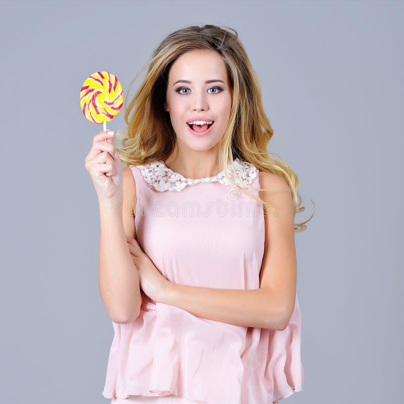 Mooie jonge vrouw die pret met een suikergoed hebben royalty-vrije stock fotografie