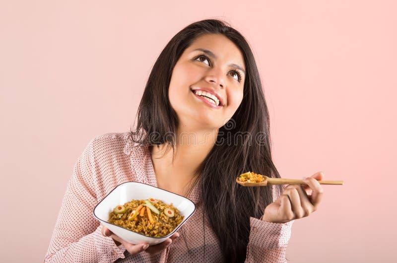 Mooie jonge vrouw die rijst het glimlachen eten stock fotografie