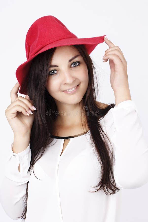 Mooie jonge vrouw die rode hoed dragen royalty-vrije stock afbeelding
