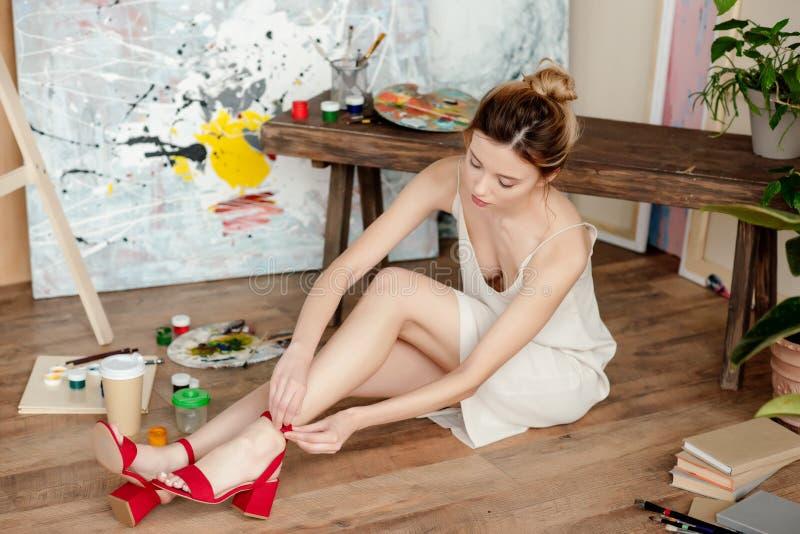 mooie jonge vrouw die rode sandals dragen terwijl het zitten op vloer royalty-vrije stock foto's