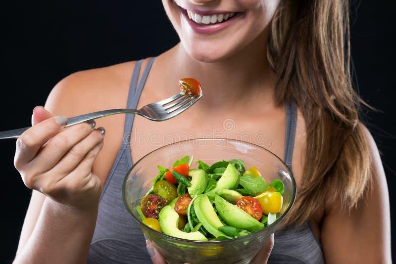 Mooie jonge vrouw die salade over zwarte achtergrond eten stock afbeelding