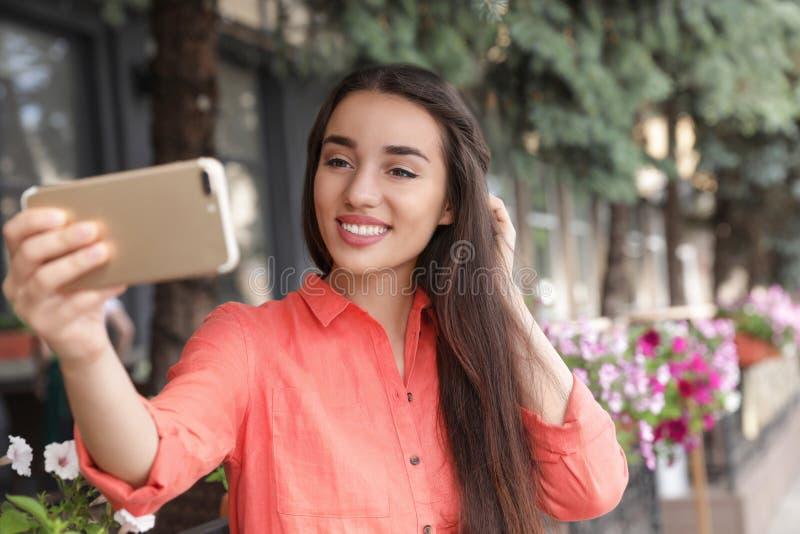 Mooie jonge vrouw die selfie in openlucht op zonnig nemen royalty-vrije stock afbeelding
