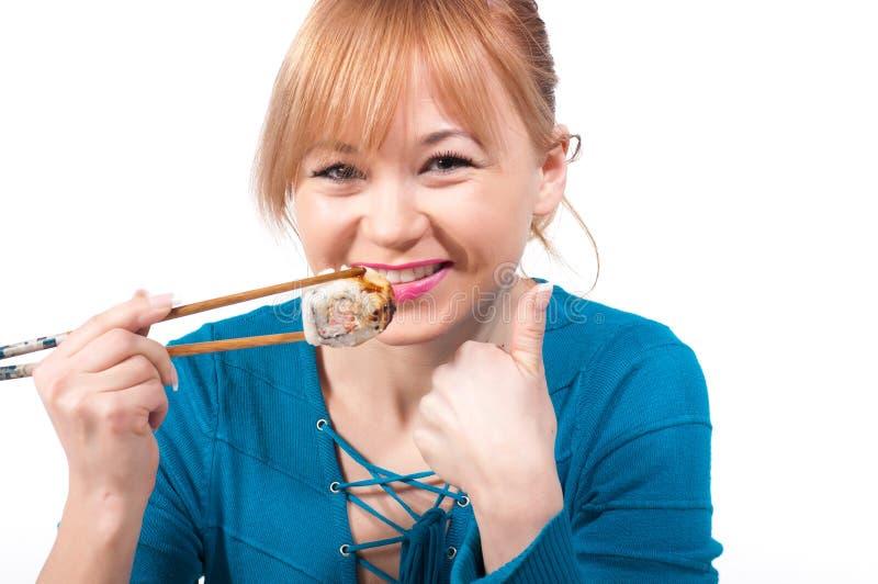 Mooie jonge vrouw die sushi met eetstokjes eten royalty-vrije stock fotografie
