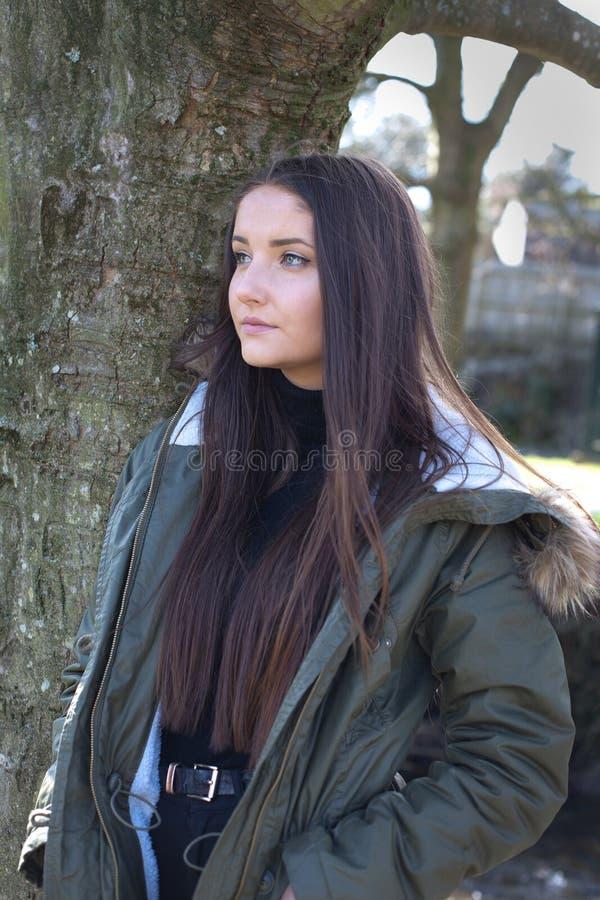 Mooie jonge vrouw die tegen een boom leunen stock afbeeldingen
