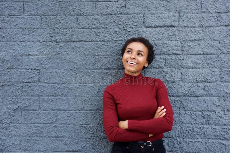 Mooie jonge vrouw die tegen grijze muur met gekruiste wapens glimlachen royalty-vrije stock afbeelding