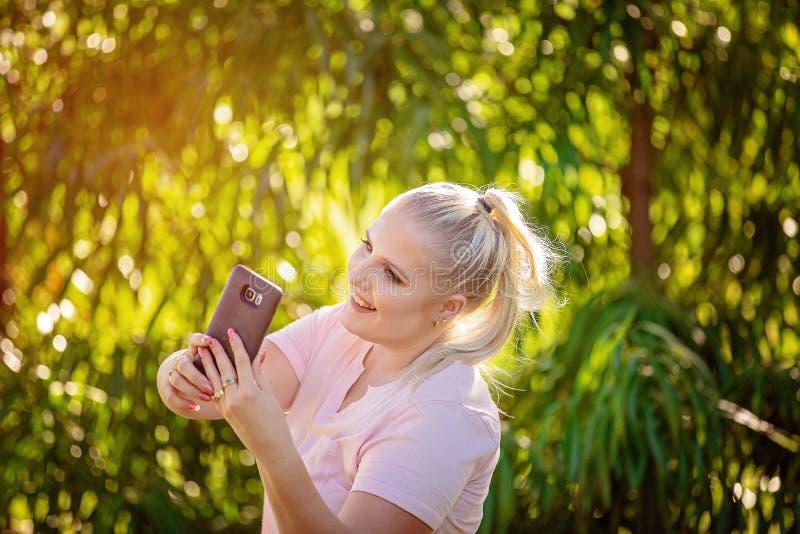 Mooie Jonge Vrouw die Telefoon in Tuin bekijken royalty-vrije stock foto's