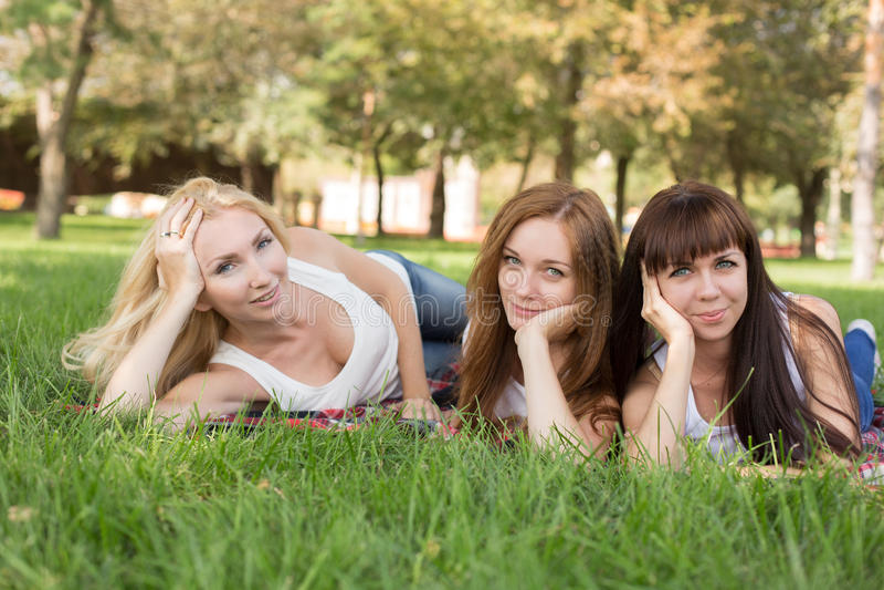 Mooie jonge vrouw die terwijl het liggen op de plaid in het park stellen stock foto