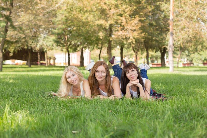 Mooie jonge vrouw die terwijl het liggen op de plaid in het park stellen royalty-vrije stock foto