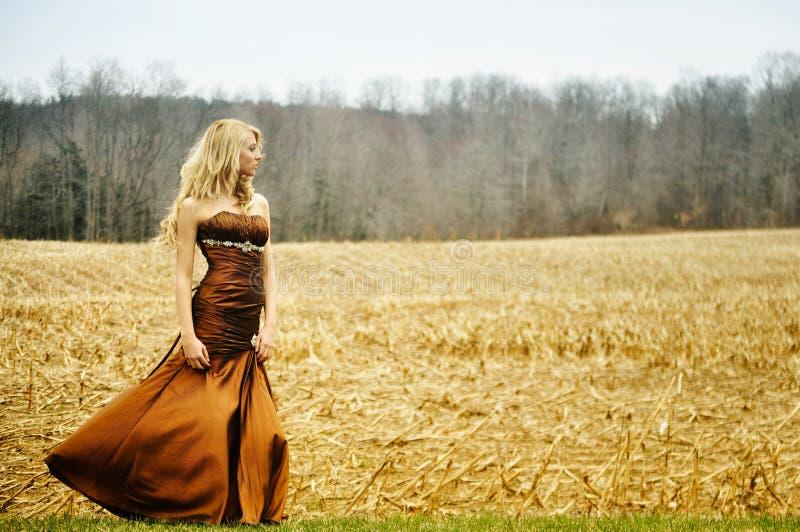 Mooie jonge vrouw die toga op een gebied draagt royalty-vrije stock foto