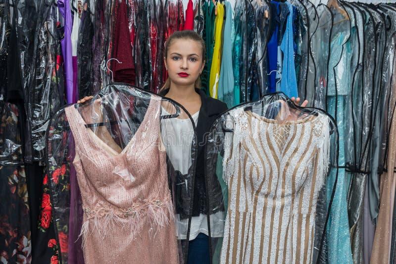 Mooie jonge vrouw die tussen twee roze kleding kiezen royalty-vrije stock afbeelding