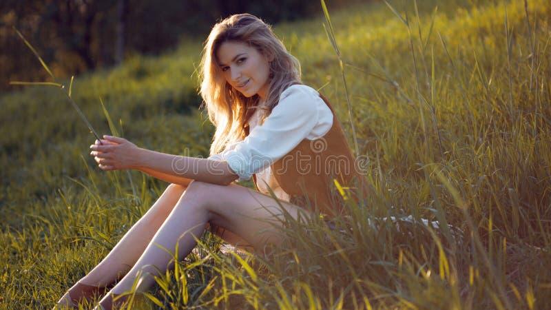 Mooie jonge vrouw die van een picknick in aard genieten Meisjeszitting op gras, rust, ontspanning royalty-vrije stock foto