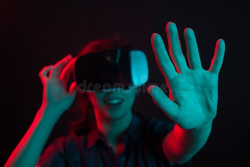 Mooie jonge vrouw die van moderne levensstijl met virtuele werkelijkheidshelm genieten in studio met creatieve verlichting stock foto