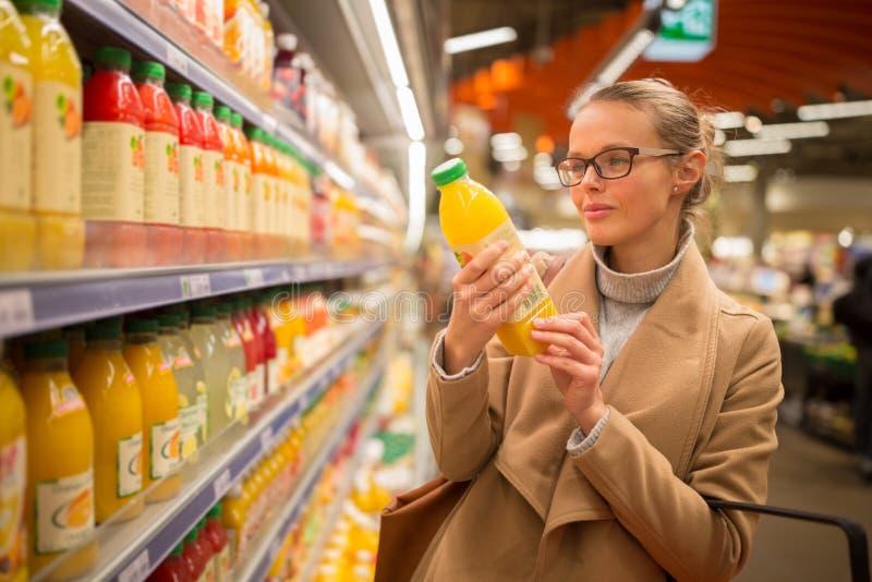 Mooie, jonge vrouw die voor haar favoriet vruchtensap winkelen royalty-vrije stock afbeelding