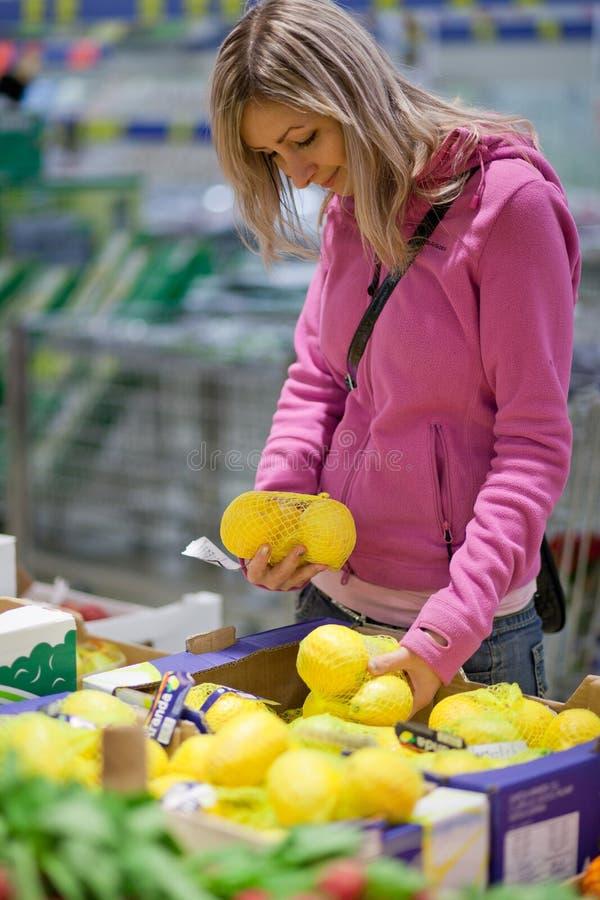 Mooie jonge vrouw die voor vruchten winkelt stock foto's