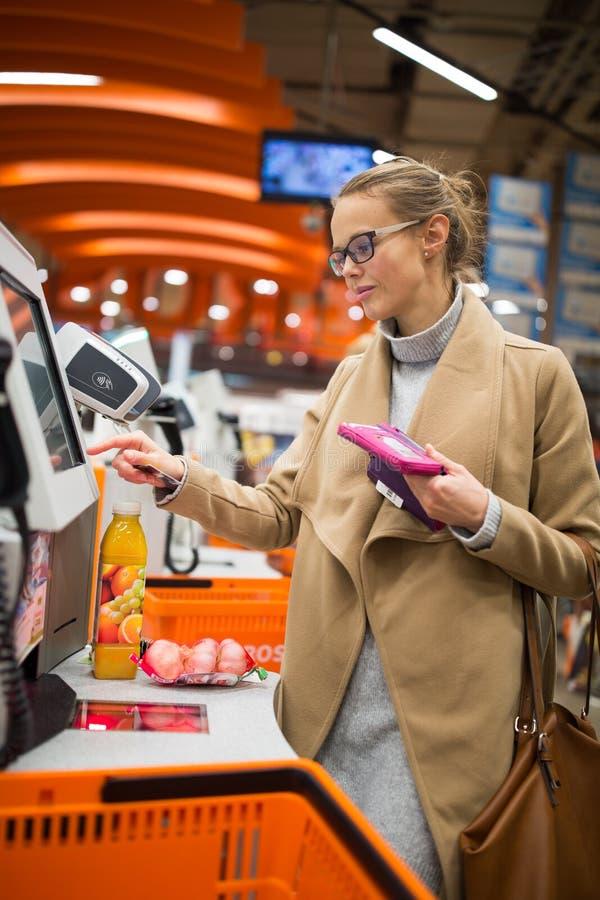 Mooie, jonge vrouw die voor wat fruit winkelen en smoothie royalty-vrije stock foto's